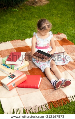 Pretty girl with photo album sitting on plaid at park