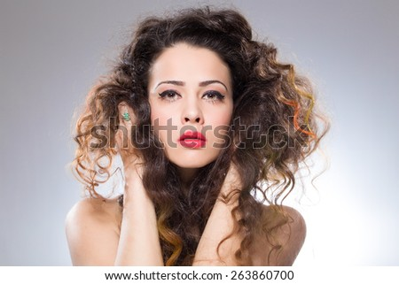 Pretty girl with red lipstick holding her curved hair - stock photo