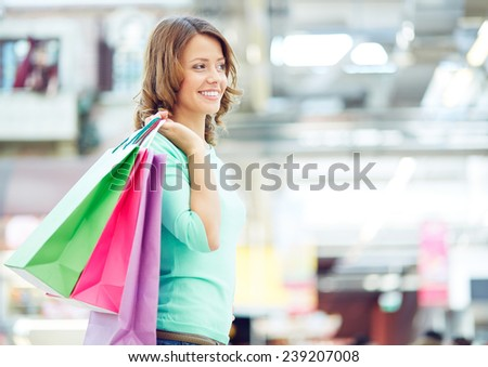 Pretty girl with shopping bags spending time in trade center - stock photo