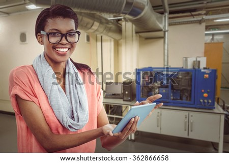 Pretty girl with tablet against factory