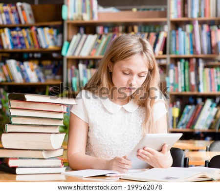 pretty girl with tablet computer working in library - stock photo