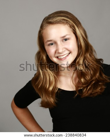 pretty girl with wavy hair on gray background - stock photo