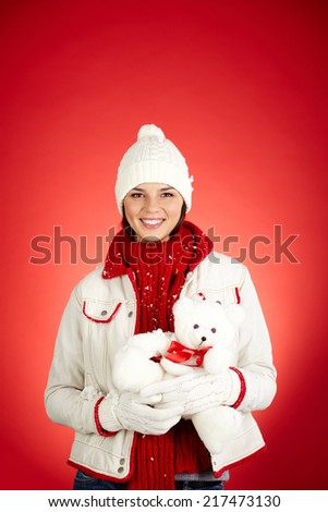 Pretty girl with white teddy bear looking at camera