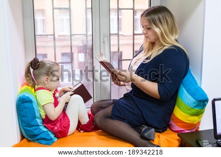 Pretty girl with young mother read books on the window sill - stock photo