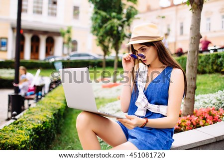 Pretty girl working with laptop sitting on stairs of city street. Urban life concept