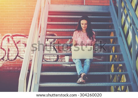 Pretty girl working with laptop sitting on stairs of stairway - stock photo