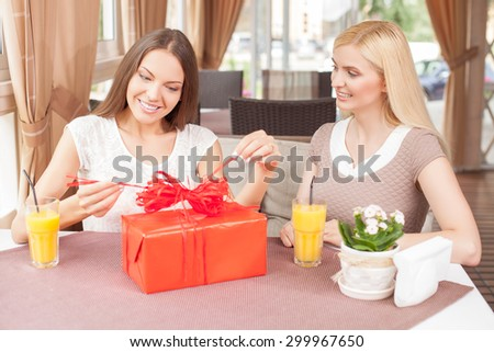 Pretty girls are celebrating birthday in restaurant. One girl is opening a gift from her friend with interest. The ladies are sitting at the table and smiling - stock photo