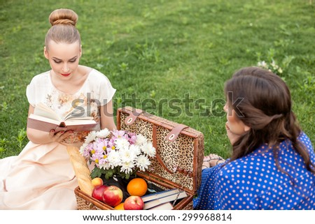 Pretty girls are sitting on grass and relaxing. The blond girl is reading a book with interest and gently smiling. He friend is looking at her pensively. There is basket of food near them - stock photo