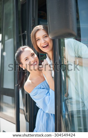Pretty girls are standing on doorsteps of a bus. They are embracing and laughing. The girls are looking through the doors of vehicle with joy - stock photo