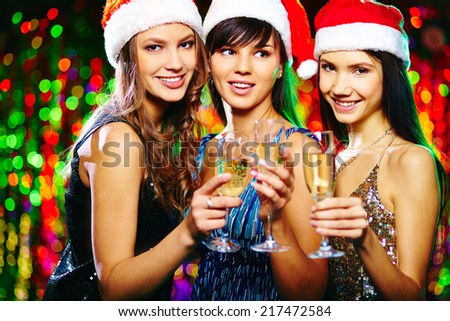 Pretty girls in Santa caps toasting at Christmas party and looking at camera with smiles - stock photo