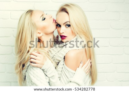 Pretty girls or two sexy cute women with blond hair and beautiful makeup in casual knitted clothes embrace on white brick wall