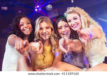 Pretty girls pointing with finger in a nightclub