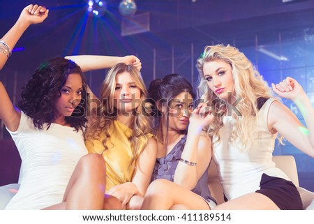 Pretty girls posing and smiling in a nightclub