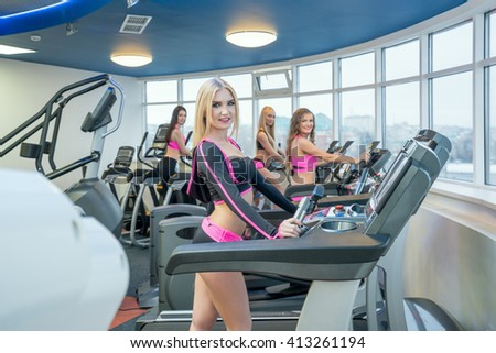 Pretty girls posing while exercising at gym