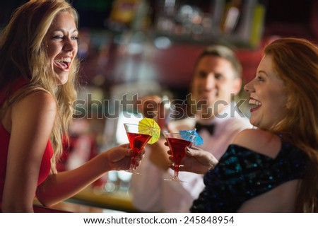Pretty girls toasting with cocktails in a bar - stock photo