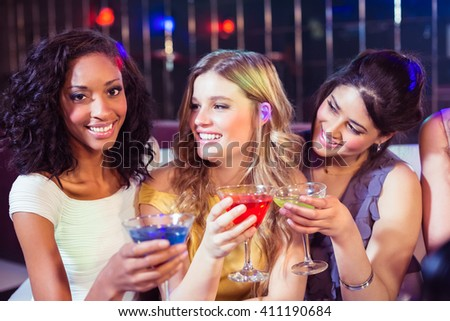 Pretty girls with cocktails in a club