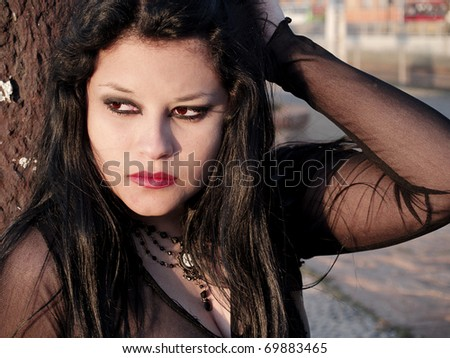 Pretty gothic woman relaxing at sunset, portrait