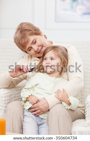 Pretty grandmother is combing hair of her granddaughter. They are sitting on chair at home and smiling. The woman is looking at the girl with love