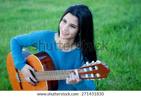 Pretty guitarist playing the guitar sitting on the grass - stock photo