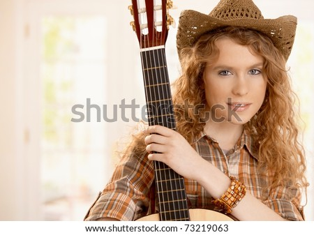 Pretty guitarplayer girl embracing her guitar, dressed in country style.? - stock photo