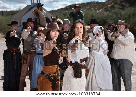 Pretty gunfighters lead armed crowd outside in American west town - stock photo