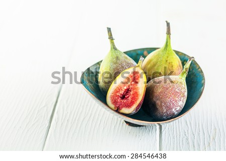Pretty handmade green pottery bowl of ripe fresh juicy succulent figs for a healthy snack on rustic white wooden boards with copyspace - stock photo