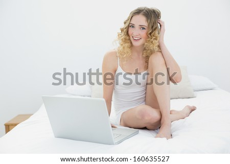 Pretty happy blonde sitting on bed using laptop in bright bedroom