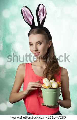 Pretty, happy blonde woman with long hair and rabbit ears on the head. She is holding bucket of little Easter eggs. - stock photo