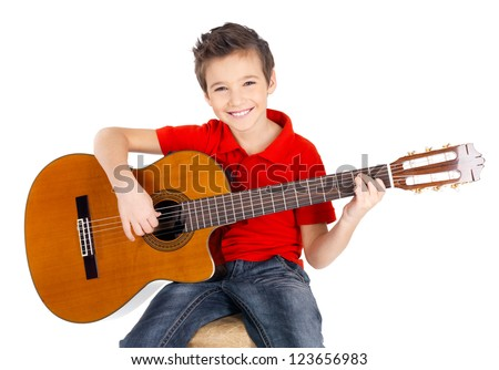 Pretty happy  boy is playing on acoustic guitar - isolated on white background