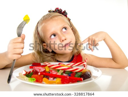 pretty happy Caucasian female child eating dish full of candy holding fork  in sweet sugar abuse dangerous diet and unhealthy nutrition concept isolated on white background - stock photo