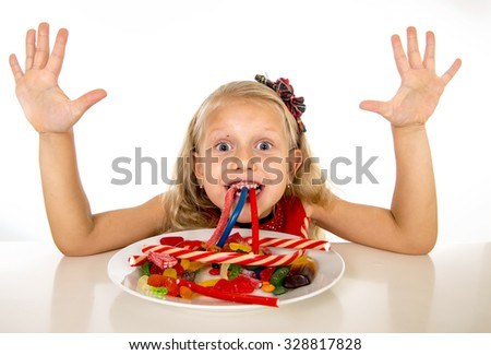 pretty happy Caucasian female child eating dish full of candy in sweet sugar abuse dangerous diet and unhealthy nutrition concept isolated on white background - stock photo