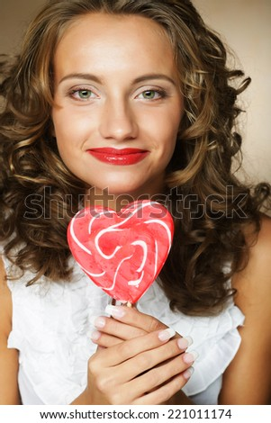 pretty happy curly girl with a lollipop in her hand  - stock photo
