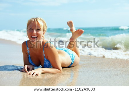 pretty happy girl lying in surf on the beach