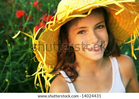 Pretty happy girl wearing a hat, poppy flowers in the background