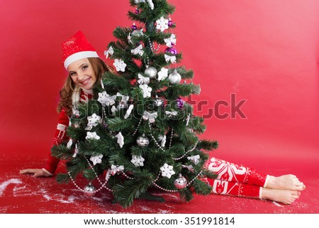 Pretty happy girl with funny grimace is looks out from behind christmas tree - stock photo
