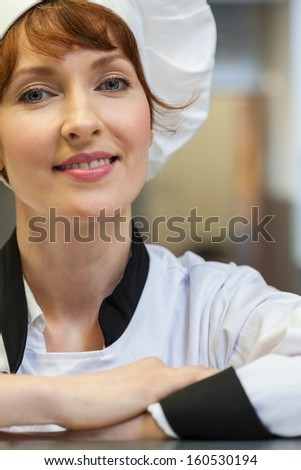 Pretty happy head chef looking at camera in professional kitchen - stock photo