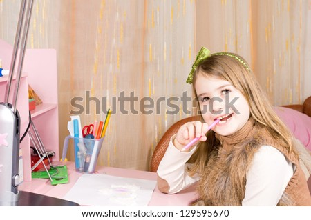 Pretty happy little girl seated at her pink desk chewing her pencil looking up at the ceiling daydreaming with a beautiful smile on her face - stock photo