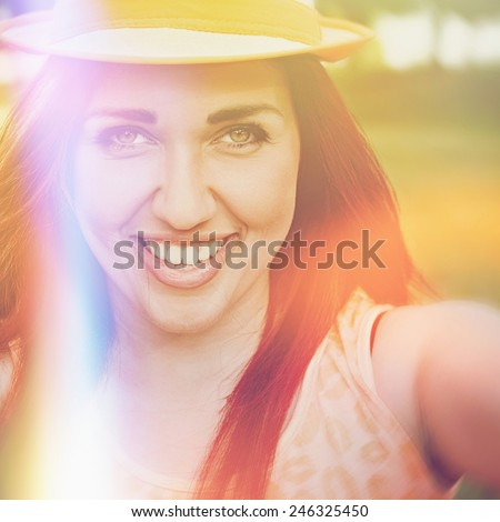 Pretty happy redhead teenage girl with hat smiling taking a selfie outdoors in park on sunny summer day. Square format, filter, saturated colors, light leak effect. - stock photo