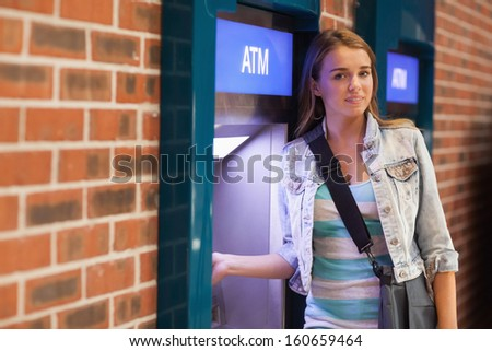 Pretty happy student withdrawing cash smiling at camera at an ATM - stock photo