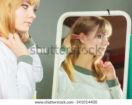 Pretty happy woman in mirror adjusting hair with clothing from new collection wardrobe. Young undecided shopper girl choosing in second hand. Shopping sale concept.