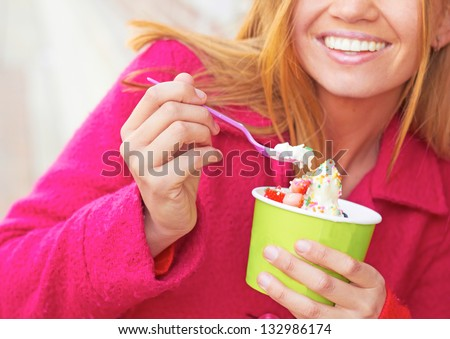 Pretty happy young pretty female eating frozen yogurt. Horizontal Shot. - stock photo