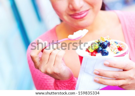 Pretty happy young pretty mixed race female eating frozen yogurt while looking away. Horizontal Shot. - stock photo