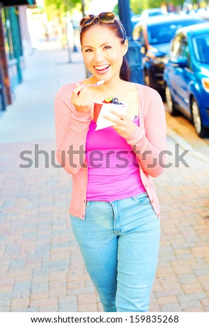 Pretty happy young pretty mixed race female eating frozen yogurt while looking away. Vertical Shot. - stock photo