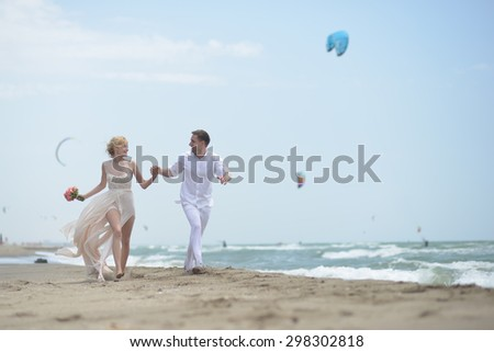 Pretty happy young wedding couple of boy and girl in white running along ocean beach coast on windy weather sunny day with paraplanes on blue sky background, horizontal picture