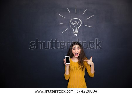 Pretty happy young woman holding and pointing on smartphone blank screen standing over chalkboard background - stock photo