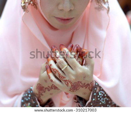 Pretty henna hands in prayer during the ceremony