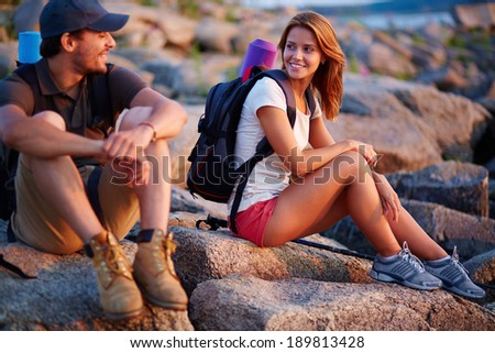 Pretty hiker looking at her boyfriend while talking to him - stock photo