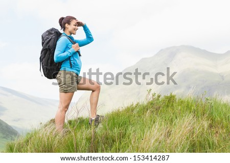 Pretty hiker with backpack walking uphill and looking ahead in the countryside