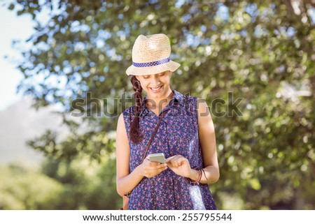 Pretty hipster checking her phone on a summers day - stock photo