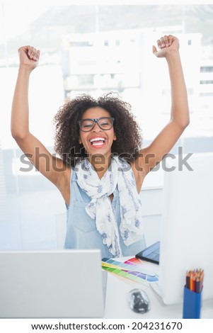 Pretty hipster cheering at her desk with laptop in her office - stock photo